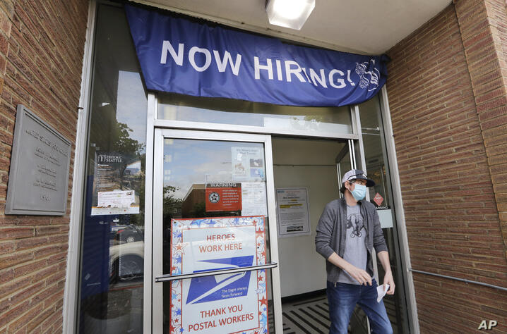 FILE - In this Thursday, June 4, 2020 file photo, a customer walks out of a U.S. Post Office branch and under a banner…