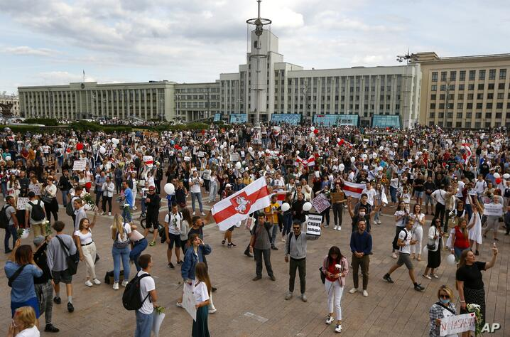 People, many holding old Belarusian national flags as they gather at Independent Square in the center of Minsk, Belarus, Friday…