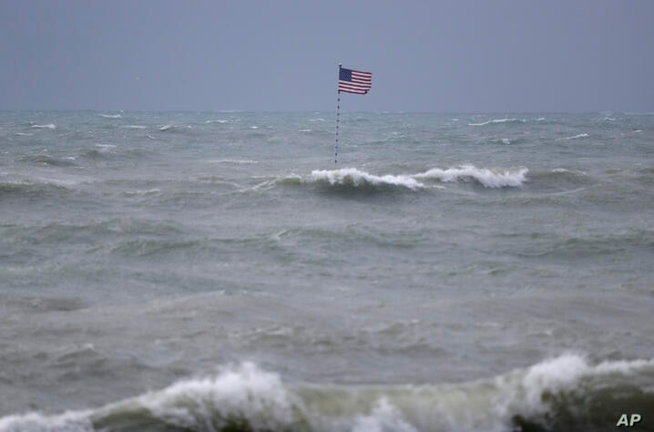 An American flag flies from the shipwreck of the Breconshire, as waves churned up by Tropical Storm Isaias crash around it,…