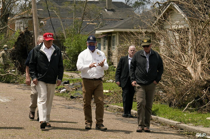 President Donald Trump listens to Louisiana Gov. John Bel Edwards, center, as he tours damage from Hurricane Laura, Saturday,…