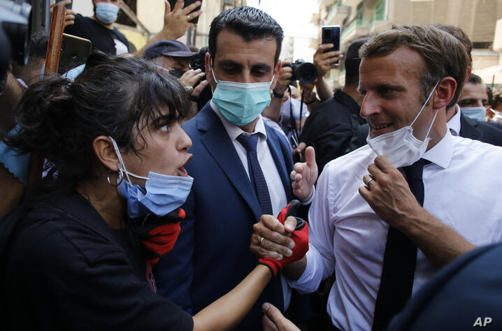 French President Emmanuel Macron listens to a resident as he visits a devastated street of Beirut, Lebanon, Thursday Aug.6,…