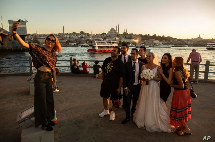 In this Friday, July 26, 2019 photo, tourists from Iran take photographs on the Galata Bridge over the Golden Horn in Istanbul…