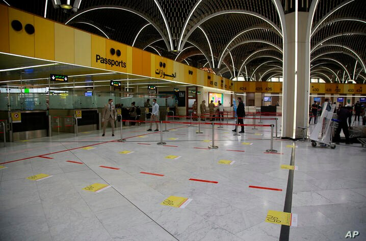 Signs are placed on the floor to avoid grouping among travelers to help prevent the spread of the coronavirus at an airport in…
