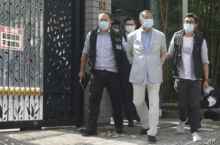 Hong Kong media tycoon Jimmy Lai, center, who founded local newspaper Apple Daily, is arrested by police officers at his home…