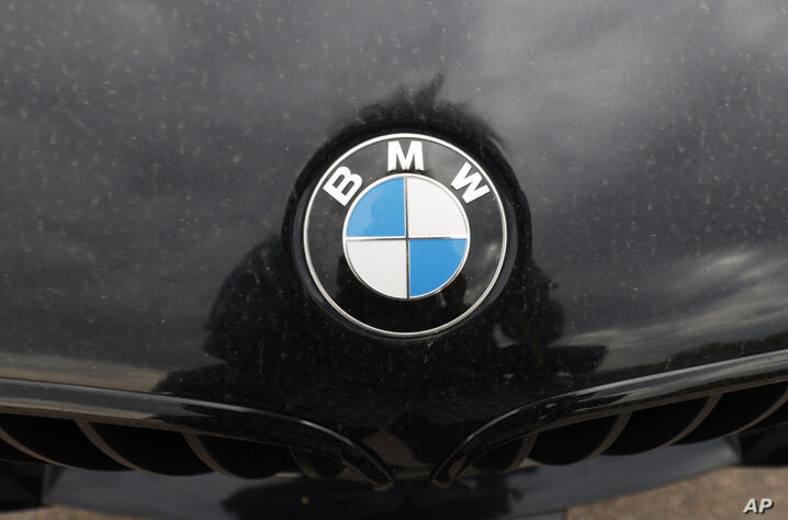 In this Sunday, June 28, 2020, photograph, the company logo shones off the hood of an unsold 2020 5-series sedan at a BMW…