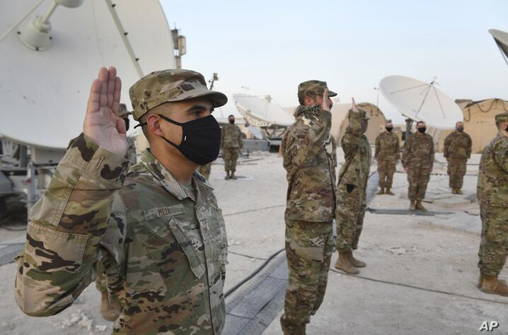 In this photo released by the U.S. Air Force, Airmen deployed to Al-Udeid Air Base, Qatar, raise their right hands during an…