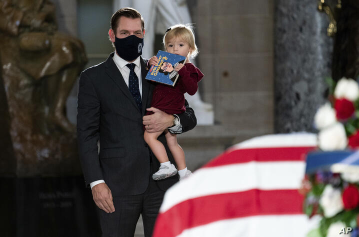 Rep. Eric Swalwell, D-Calif., and his daughter Kathryn  pay their respects as the flag-draped casket of Justice Ruth Bader…