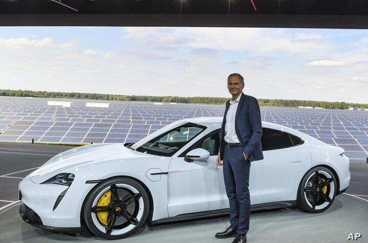Porsche CEO Oliver Blume stands next to a Porsche Taycan, the first purely electric driven car of the German car maker, during…