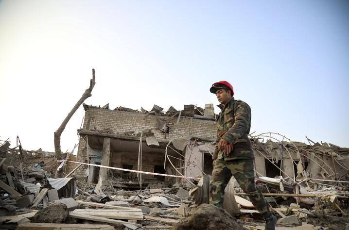 A soldier walks past a destroyed house in a residential area that was hit by rocket fire overnight by Armenian forces, early…