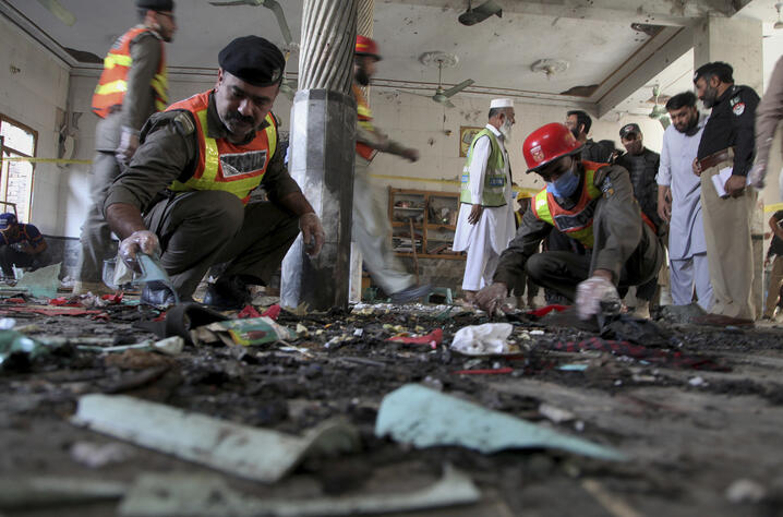 Pakistani rescue workers and police officers examine the site of a bomb explosion in an Islamic seminary, in Peshawar, Pakistan…