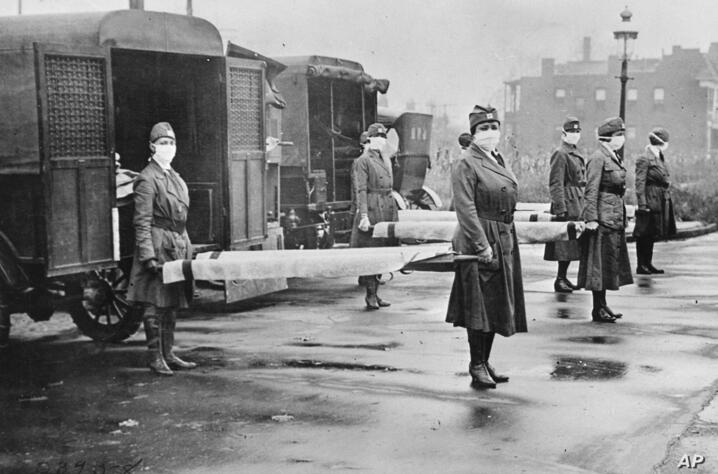 In this October 1918 photo made available by the Library of Congress, St. Louis Red Cross Motor Corps personnel wear masks as…