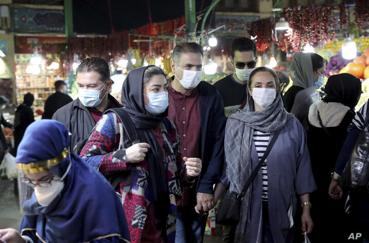 People wear protective face masks to help prevent the spread of the coronavirus in the Tajrish traditional bazaar in northern…