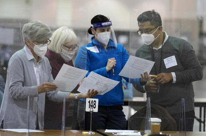 Election officials read documents before a hand recount of ballots at the Wisconsin Center, Friday, Nov. 20, 2012, in Milwaukee…