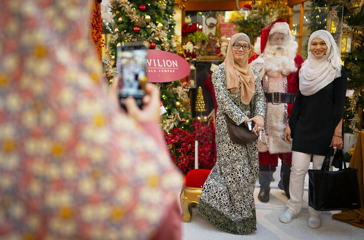 Muslim women pose for pictures with a man dressed in a Santa Claus outfit, as he wears a face shield and stands behind a…