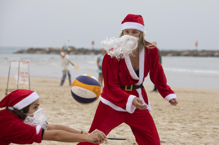 People dressed in Santa Claus costumes play volleyball at the beach in Tel Aviv, Israel, Tuesday, Dec. 22, 2020. (AP Photo…