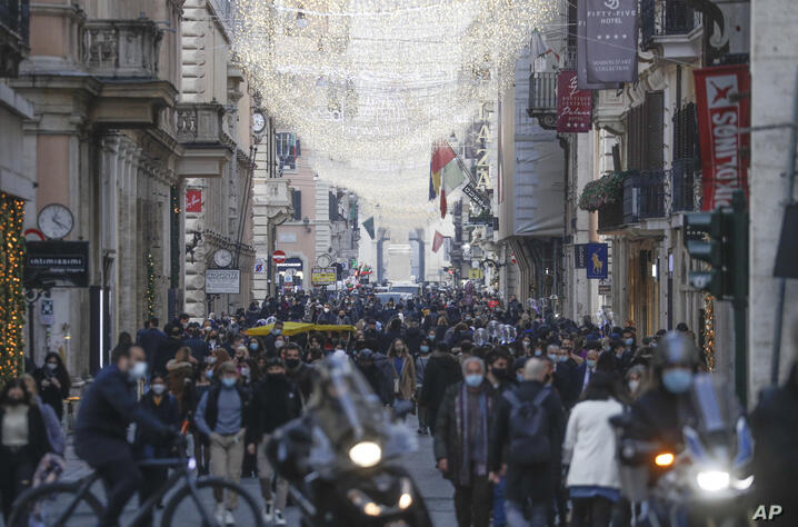 People crowd Via del Corso shopping street ahead of a Christmas eve national lockdown due to start on Dec. 24, in Rome,…