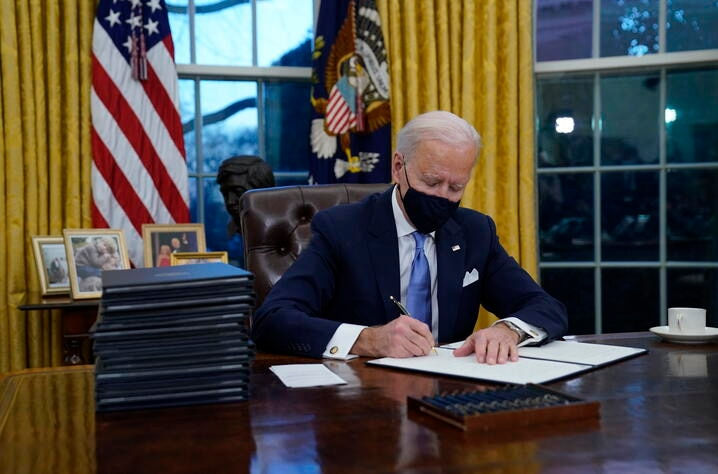 President Joe Biden signs his first executive orders in the Oval Office of the White House on Wednesday, Jan. 20, 2021, in…