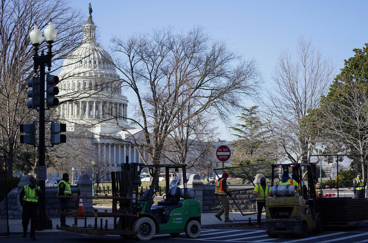 With the U.S. Capitol in the background, workers place fencing around the Capitol grounds the day after violent protesters…