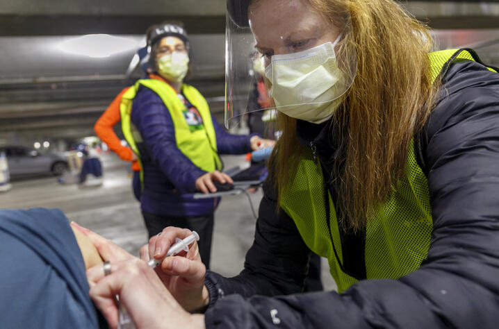 Pharmacist Colleen Naughtin, right, administers the Moderna COVID-19 vaccine at a drive-thru vaccination clinic in Portland,…