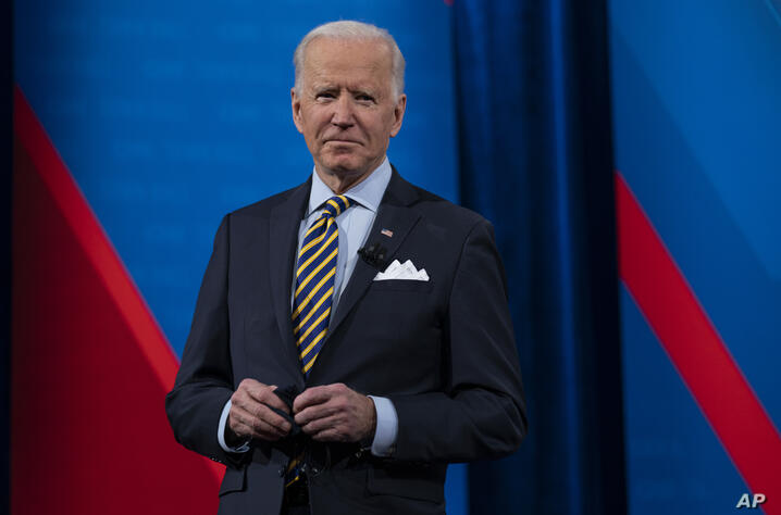 President Joe Biden talks with audience members as he waits for a commercial break to end during a televised town hall event at…