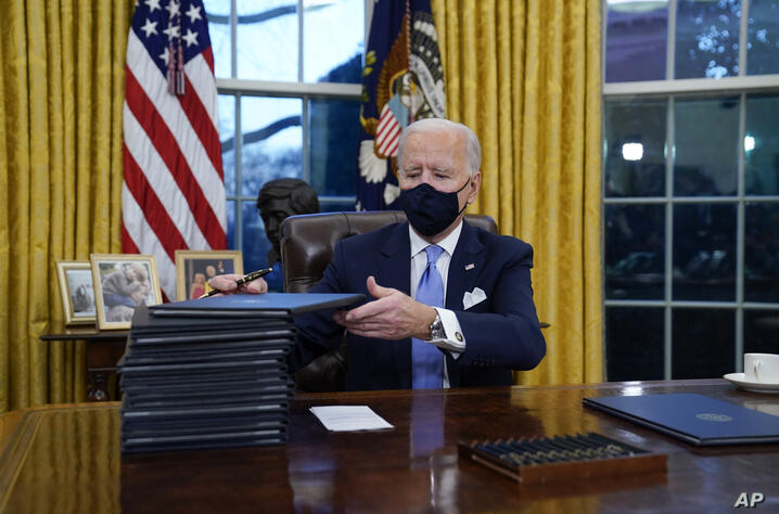 FILE - In this Jan. 20, 2021, file photo, President Joe Biden signs his first executive orders in the Oval Office of the White…