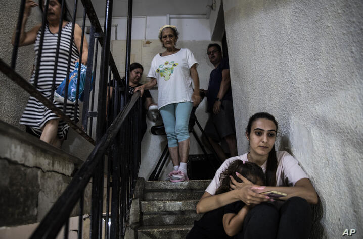 People in Ashdod, Israel take shelter in the stairwell of their apartment building during a siren warning of rockets fired from…
