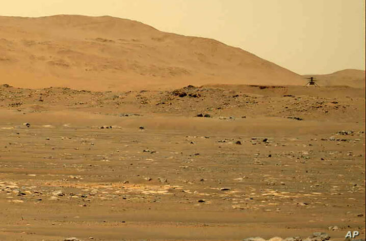 In this image taken by the Mars Perseverance rover and made available by NASA, the Mars Ingenuity helicopter, right, flies over…