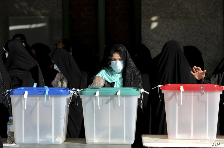 Voters cast their ballots for the presidential election at a polling station in Tehran, Iran, Friday, June 18, 2021. Iran began…