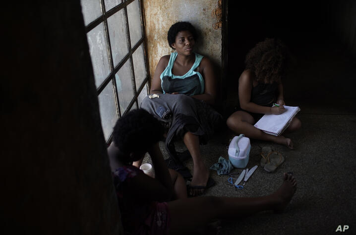 A mother sits on a window seat as she accompanies her daughter inside an occupied building where they live, in Rio de Janeiro,…