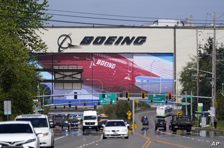 Traffic drives in view of a massive Boeing Co. production plant, where images of jets decorate the hangar doors, Friday, April…