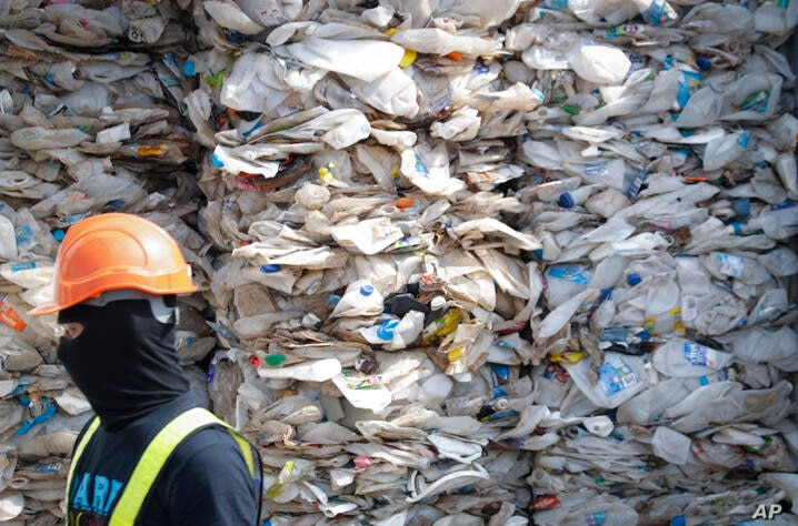 FILE - In this May 28, 2019, file photo, a container is filled with plastic waste from Australia, in Port Klang, Malaysia…