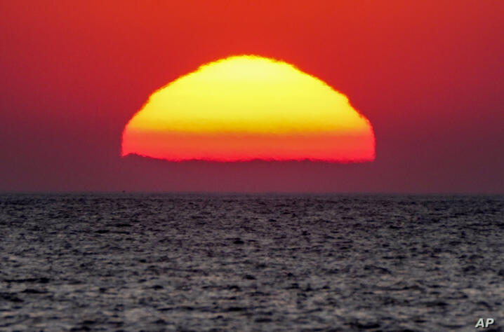 The sun rises over the Baltic Sea viewed from Timmendorfer Strand, Germany, Thursday, June 3, 2021. (AP Photo/Michael Probst)