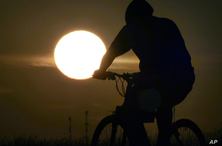 An unidentified bicycle rider pedals west along US 40 near Lawrence, Kan., Monday, July 11, 2011. Heat advisories and excessive…