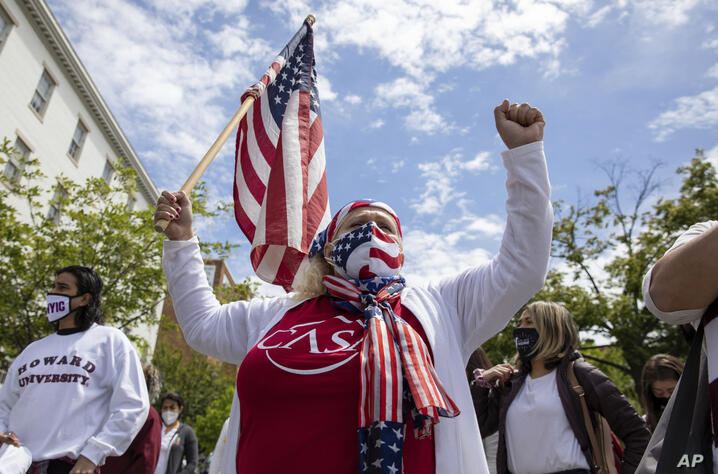 FILE - In this May 12, 2021 file photo, Ivania Castillo raises her fist during a a protest for the immigration reform with the…