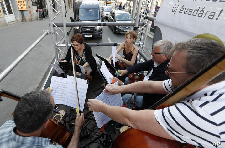 Members of Budapest Festival Orchestra are playing classical music on the back of a track while driving through downtown…