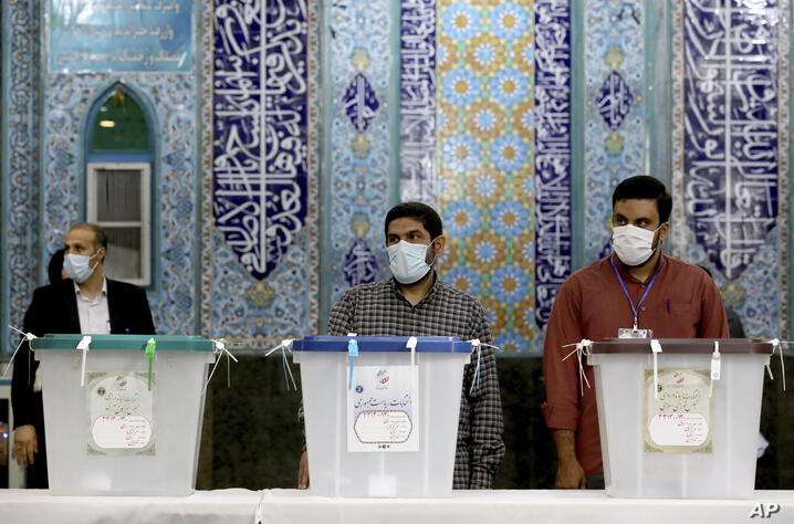 Iranian election officials wait for voters during the presidential election at a polling station in Tehran, Iran, Friday, June…