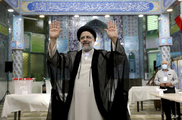 Ebrahim Raisi, a candidate in Iran's presidential elections waves to the media after casting his vote at a polling station in…