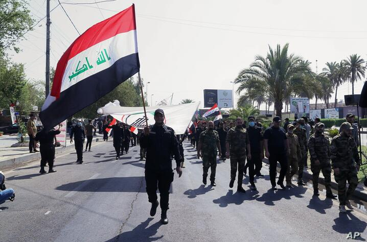 Iran-backed militia fighters march in central Baghdad, Iraq, Tuesday, June 29, 2021. Iraqi Shiite militias are showing a degree…