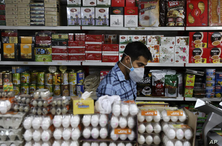 Shopkeeper Tohid Vatanparast, wearing a protective face mask to help prevent the spread of the coronavirus, works at his…