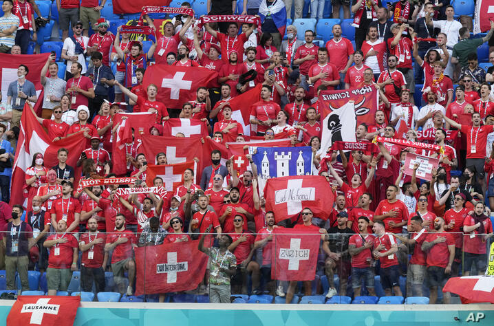 Switzerland supporters hold up their flags and scarves during the Euro 2020 soccer championship quarterfinal match between…