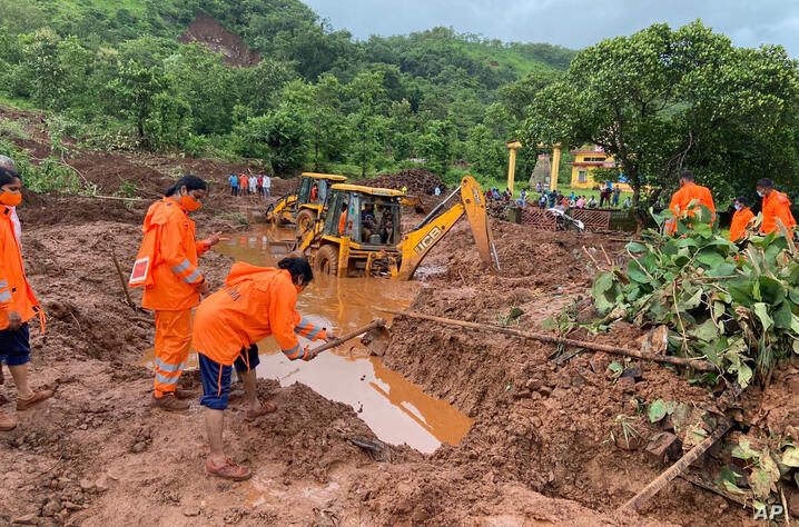 This photograph provided by India's National Disaster Response Force (NDRF) shows NDRF women personnel engaged in rescue work…