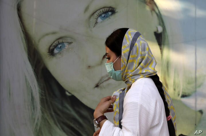 A woman wearing protective face mask to help prevent the spread of the coronavirus walks past an advertisement of skin care…