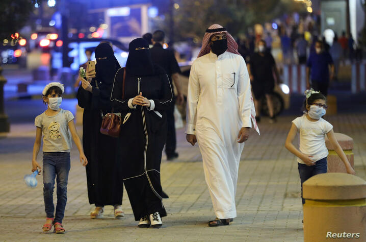 A Saudi family wearing protective face masks walk on Tahlia Street as nightlife kicks off, after the government loosened lockdown restrictions following the outbreak of the coronavirus disease (COVID-19), in Riyadh