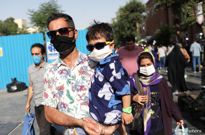 An Iranian man and his son wearing a protective face mask walks in a street, following the outbreak of the coronavirus disease (COVID-19), in Tehran