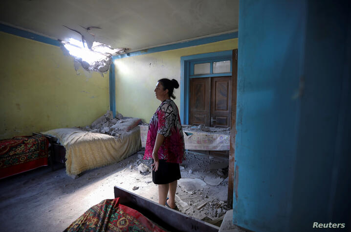 FILE PHOTO: A woman stays in a house damaged by a recent shelling in armed clashes on the border between Azerbaijan and Armenia, in the village of Dondar Quschi