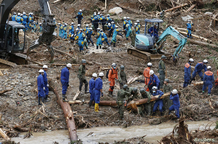 Rescue workers search for missing people at a landslide site caused by torrential rain in Tsunagi town