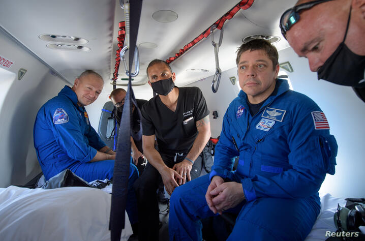 NASA astronauts Douglas Hurley and Robert Behnken prepare to depart their helicopter at Naval Air Station Pensacola after the duo landed in their SpaceX Crew Dragon Endeavour spacecraft in the Gulf of Mexico off the coast of Pensacola, Florida