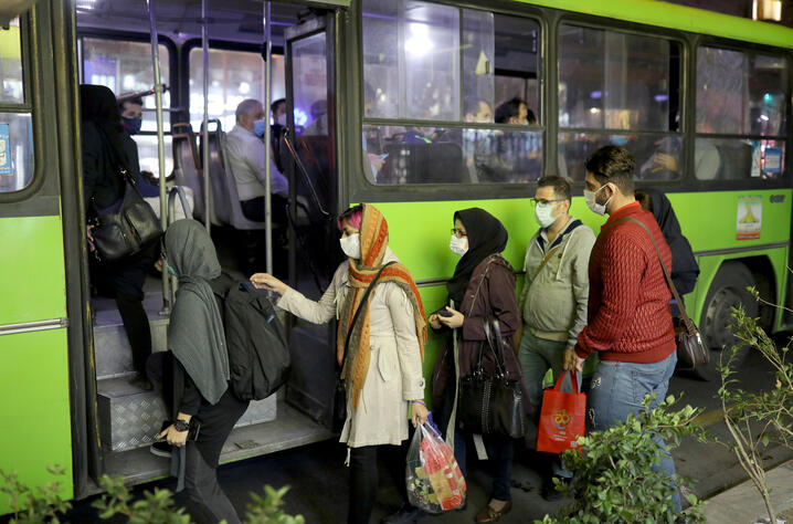 FILE PHOTO: Iranian People wearing protective masks as they board a bus, amid the outbreak of the coronavirus disease (COVID-19), in Tehran