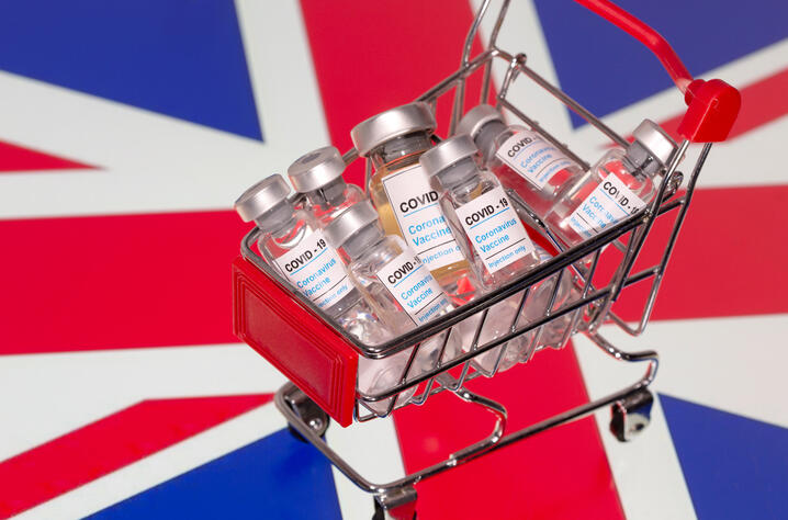 "FILE PHOTO: A small shopping basket filled with vials labeled  ""COVID-19 - Coronavirus Vaccine""  is placed on a UK flag"