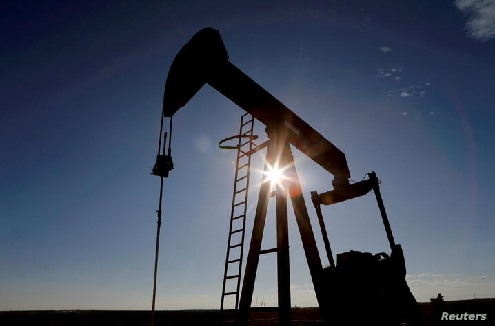 FILE PHOTO: FILE PHOTO: The sun is seen behind a crude oil pump jack in the Permian Basin in Loving County